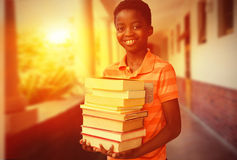 Composite image of portrait of cute boy carrying books in library Royalty Free Stock Photos