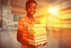 Composite image of portrait of cute boy carrying books in library Stock Photography