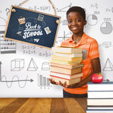 Composite image of portrait of cute boy carrying books in library. Portrait of cute boy carrying books in library against wooden surface with planks Stock Photo