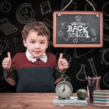 Composite image of portrait of cute boy gesturing thumbs up Royalty Free Stock Photo