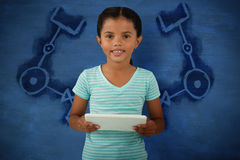 Composite image of portrait of cute smiling girl holding digital tablet. Portrait of cute smiling girl holding digital tablet against blue background Royalty Free Stock Photography