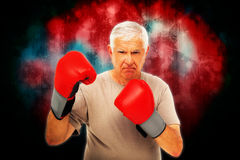 Composite image of portrait of a determined senior boxer. Portrait of a determined senior boxer against dark background Stock Photography