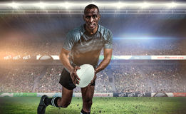 Composite image of portrait of determined sportsman running with rugby ball Royalty Free Stock Photo