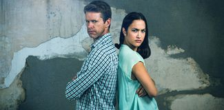 Composite image of portrait of displeased couple standing back to back. Portrait of displeased couple standing back to back against rusty weathered wall Stock Photos
