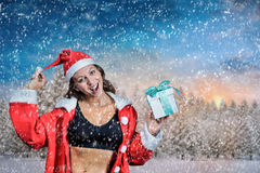 Composite image of portrait of female athlete in christmas costume and holding gift Royalty Free Stock Photo