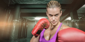 Composite image of portrait of female boxer with fighting stance Royalty Free Stock Images