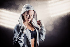 Composite image of portrait of female boxer in hood with fighting stance. Portrait of female boxer in hood with fighting stance against spotlight royalty free stock photography