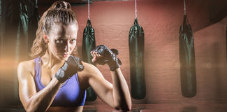 Composite image of portrait of female confident boxer with fighting stance. Portrait of female confident boxer with fighting stance against punching bags in red royalty free stock photography