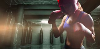 Composite image of portrait of female fighter with fighting stance. Portrait of female fighter with fighting stance against red boxing area with punching bags royalty free stock photography