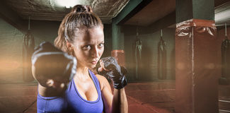 Composite image of portrait of female fighter punching Stock Photography