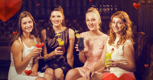 Composite image of portrait of female friends holding glasses of cocktail in bar Stock Photo