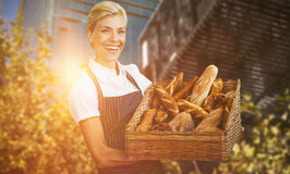 Composite image of portrait of female owner holding basket with bread Stock Image