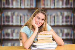 Composite image of portrait of female student in library. Portrait of female student in library against books on desk in library Royalty Free Stock Photos