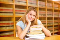 Composite image of portrait of female student in library. Portrait of female student in library against close up of a bookshelf Royalty Free Stock Images