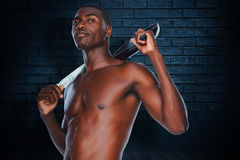 Composite image of portrait of a fit shirtless man holding frying pan Stock Photo