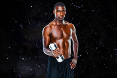 Composite image of portrait of a fit shirtless young man lifting dumbbell. Portrait of a fit shirtless young man lifting dumbbell against black background Stock Photo