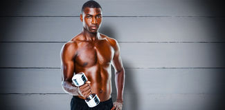 Composite image of portrait of a fit shirtless young man lifting dumbbell Stock Photography