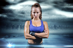 Composite image of portrait of fit woman with arms crossed. Portrait of fit woman with arms crossed against stormy sky with tornado over road Royalty Free Stock Photography