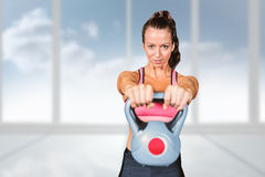 Composite image of portrait of fit woman lifting kettlebell Royalty Free Stock Photo