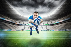 Composite image of portrait full length of american football player diving. Portrait full length of American football player diving against rugby stadium Stock Image