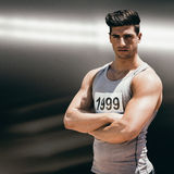 Composite image of portrait of handsome sportsman is posing with crossed arms Stock Photography