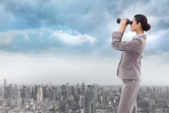 Composite image of portrait of a happy businesswoman looking through binoculars Stock Photos