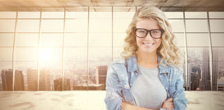 Composite image of portrait of happy businesswoman wearing eyeglasses with arms crossed Stock Photography