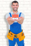 Composite image of portrait of happy construction worker holding house model Stock Image