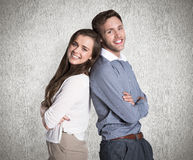 Composite image of portrait of happy couple back to back. Portrait of happy couple back to back against weathered surface Royalty Free Stock Image