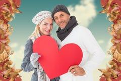 Composite image of portrait of happy couple holding heart Stock Photo