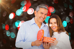 Composite image of portrait of happy couple opening present. Portrait of happy couple opening present against digitally generated twinkling light design Royalty Free Stock Image