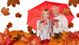 Composite image of portrait of happy couple under red umbrella Royalty Free Stock Image