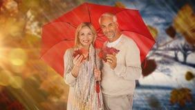 Composite image of portrait of happy couple under red umbrella Stock Photo