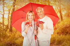 Composite image of portrait of happy couple under red umbrella Royalty Free Stock Images