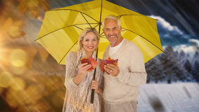 Composite image of portrait of happy couple under yellow umbrella Royalty Free Stock Photos