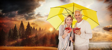 Composite image of portrait of happy couple under yellow umbrella. Portrait of happy couple under yellow umbrella against country scene Stock Images