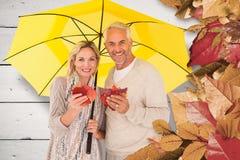 Composite image of portrait of happy couple under yellow umbrella Stock Image