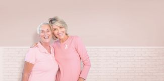 Composite image of portrait of happy daughter with mother supporting breast cancer awareness Stock Photography