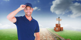 Composite image of portrait of happy delivery man wearing cap. Portrait of happy delivery man wearing cap against path on grass Stock Photography