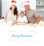 Composite image of portrait of a happy family preparing christmas cookies Stock Photo
