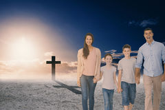 Composite image of portrait of happy family walking over white background. Portrait of happy family walking over white background against cross religion symbol Stock Photo
