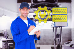 Composite image of portrait of happy male mechanic writing on clipboard. Portrait of happy male mechanic writing on clipboard against auto repair shop Royalty Free Stock Images