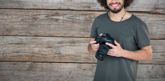 Composite image of portrait of happy male photographer holding camera. Portrait of happy male photographer holding camera against full frame of wooden wall Royalty Free Stock Photo