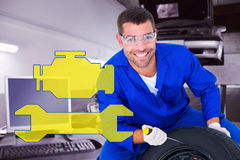 Composite image of portrait of happy mechanic working on tire Royalty Free Stock Photography