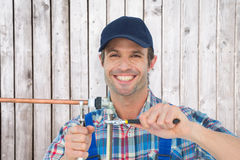 Composite image of portrait of happy plumber fixing pipe Stock Photography