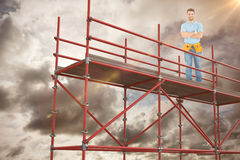 Composite image of portrait of happy repairman standing arms crossed. Portrait of happy repairman standing arms crossed against blue sky with white clouds Stock Photo