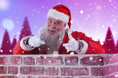 Composite image of portrait of happy santa claus making hand gesture over wall Stock Photography