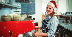 Composite image of portrait of happy waitress wearing santa hat Stock Image