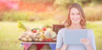 Composite image of portrait of happy woman holding digital tablet Stock Photos