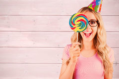 Composite image of portrait of a hipster hiding herself behind a lollipop Stock Photography